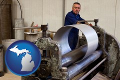 michigan map icon and a sheet metal worker fabricating a metal tube